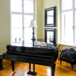 Black piano in room with big windows